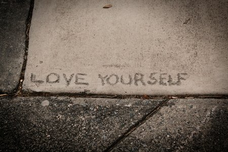 love yourself written on a sidewalk