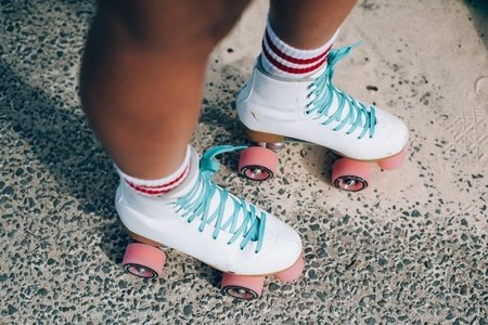white roller skates with light blue laces and pink wheels; white socks with two red stripes on each.