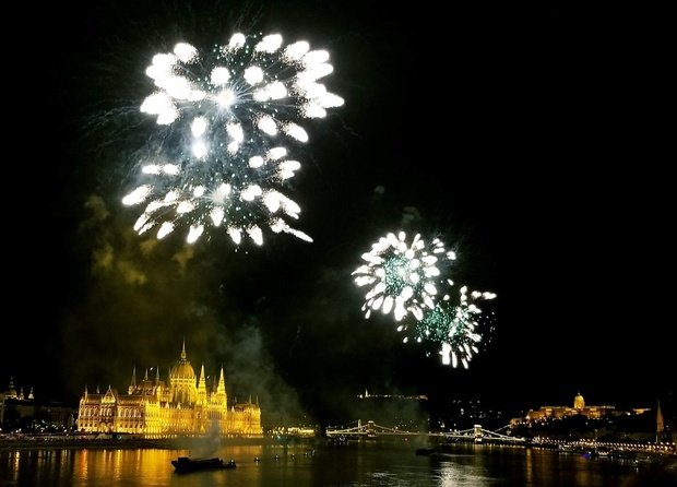 the parliament of Budapest, illuminated at night, fireworks above