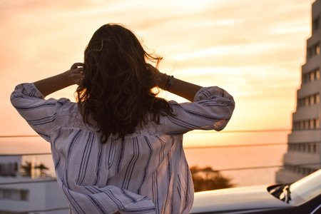woman looking at sunset over water