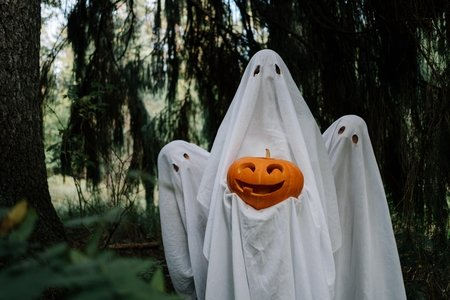 three bed sheet ghosts with a pumpkin
