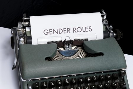 gender roles typed on paper in green typewriter