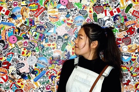 Emily Lin in front of sticker wall