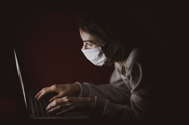 Woman with mask on laptop