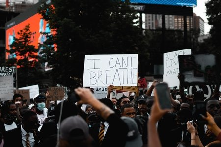 "group of protesters with someone holding a sign that says ""I can't breathe"""