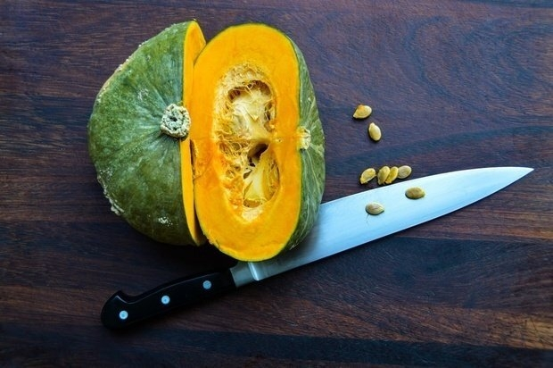 sliced green and orange squash with knife on wooden board