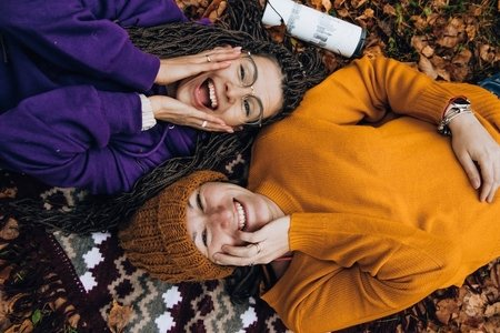 Two women laughing and laying in leaves