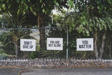 Don't give up signs in a fence