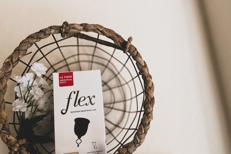 flex menstrual cup box in a basket with flowers