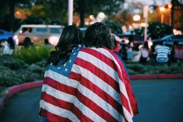 Two women wrapped in American flag