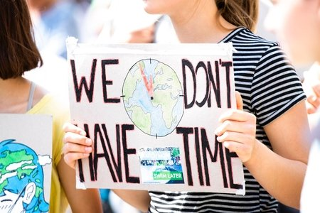 woman at climate change protest holding sign