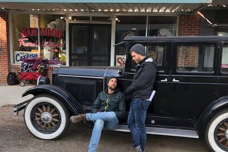 two set memebers with vintage car
