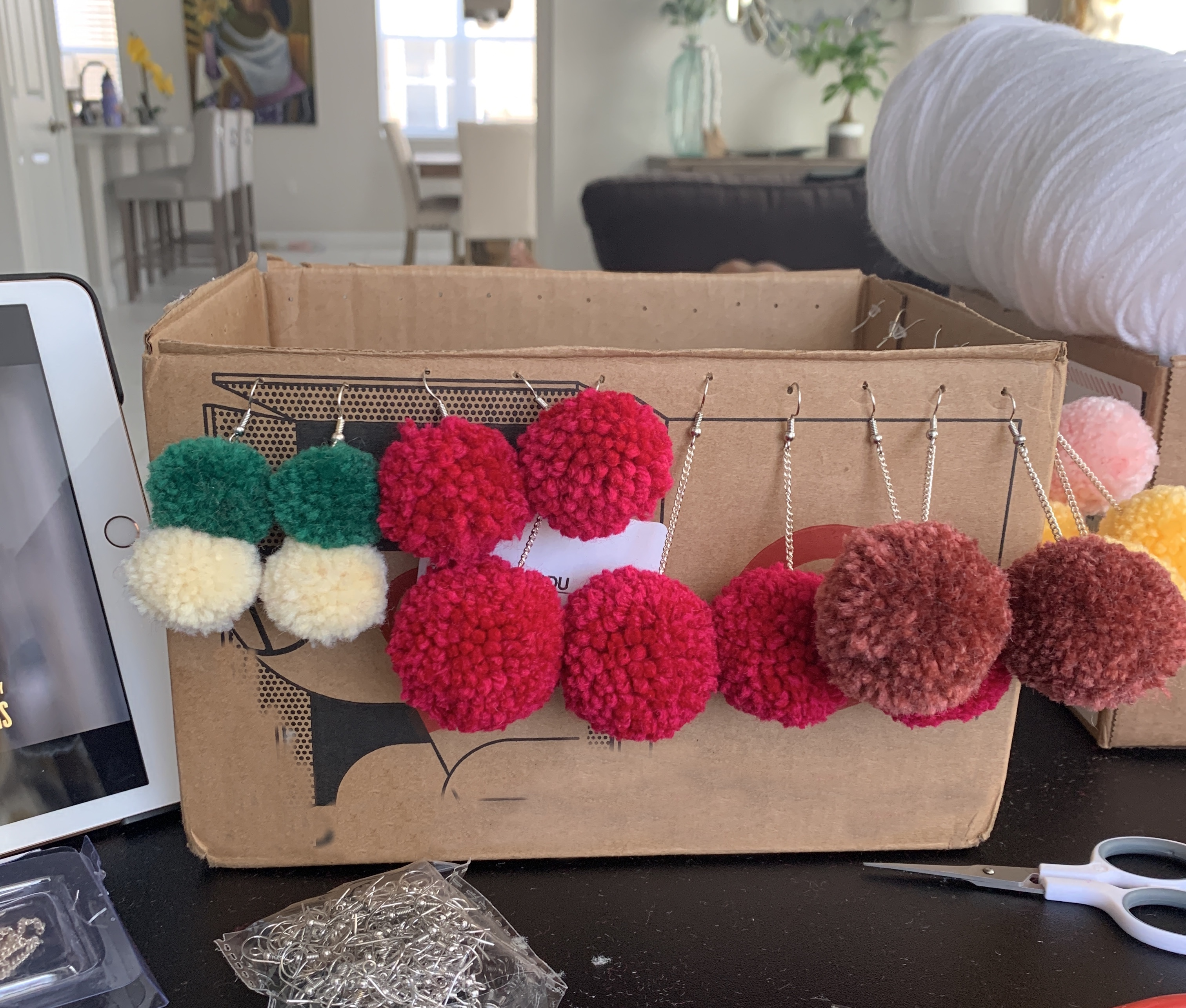 Variety of Pom-pom earrings dangling from a cardboard box