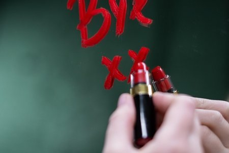 """Woman writing the word """"Bye"""" on a mirror with red lipstick"""