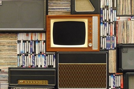 Retro wooden TV, VHS tapes and old stereos surrounding it