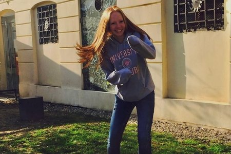 Redhead in a fighting position with her hands tucked into her hoodie sleeves