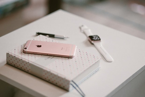 Rose gold smartphone on top of white white covered book with smartwatch