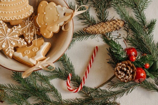 a plate of sugar cookies surrounded by candy canes, pinecones, and green.