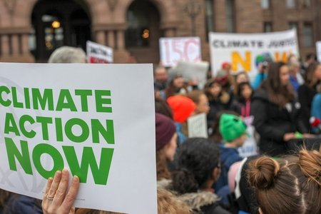 "protest sign that says ""climate action now"" in front of a crowd"