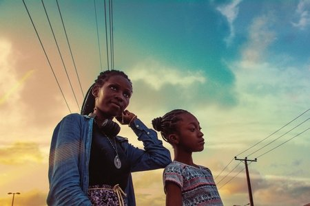 Two women with braids with the sky in the background