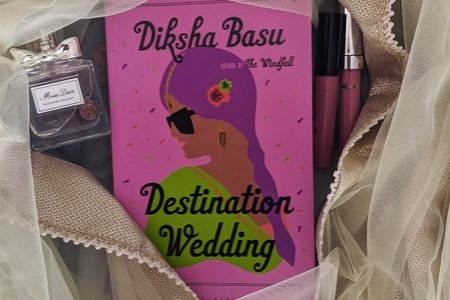 Book Destination Wedding with cloth wrapped around it with fairy lights, a perfume and lipgloss.