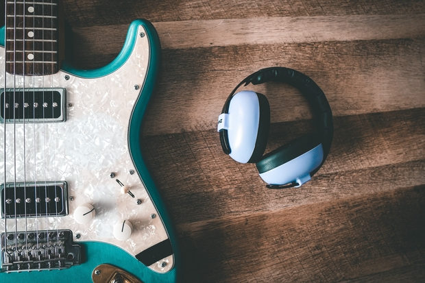 headphones next to a guitar