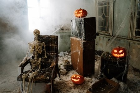 a skeleton in a chair, jack-o-lanterns, and cobwebs.