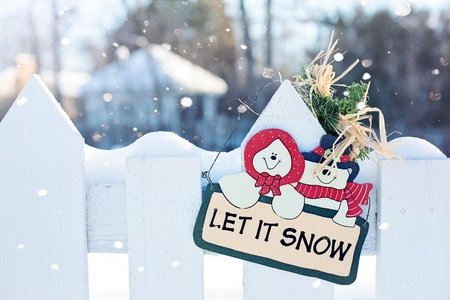 """a sign that says """"let it snow"""" with snowmen are displayed on white fence."""