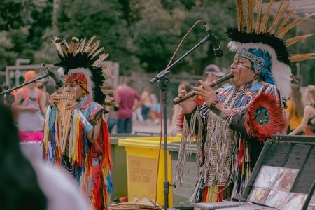 two native americans playing woodwind instruments in traditional clothing