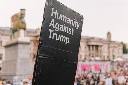 """person holding a sign that says """"humanity against Trump"""""""