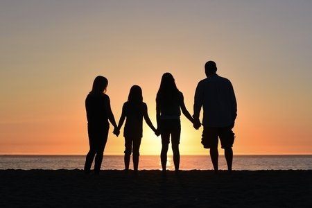 four people holding hands on the beach