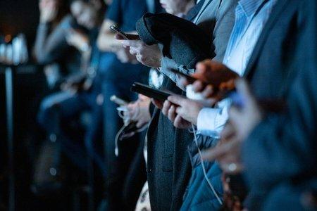 People using their phones staring down