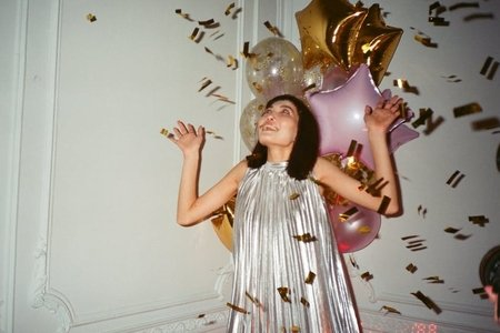 A girl in a silver dress with gold confetti and pink and gold balloons surrounding her