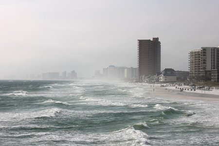 waves crashing on beach in front of buildings