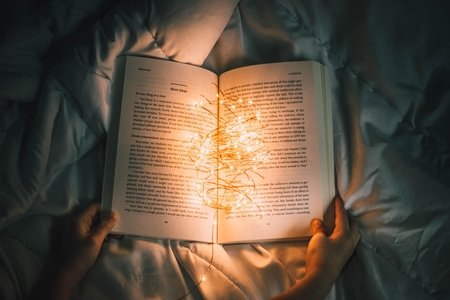 book on a bed illuminated with tiny lights