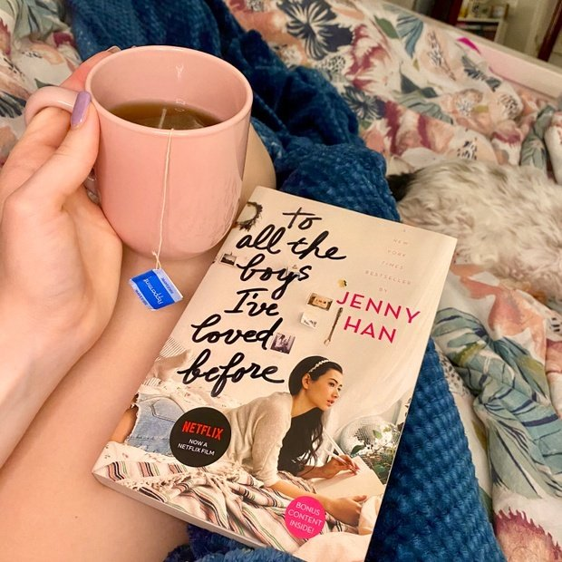 Girl with cup of tea and the book To All the Boys I've Loved Before