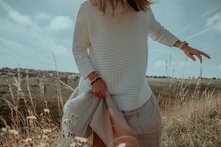 woman in white sweater and beige skirt in field