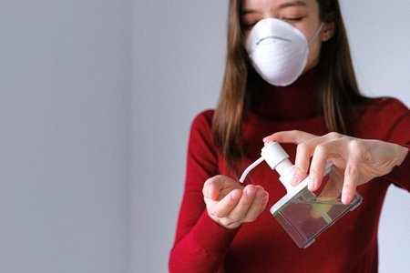 woman wearing mask using hand sanitizer