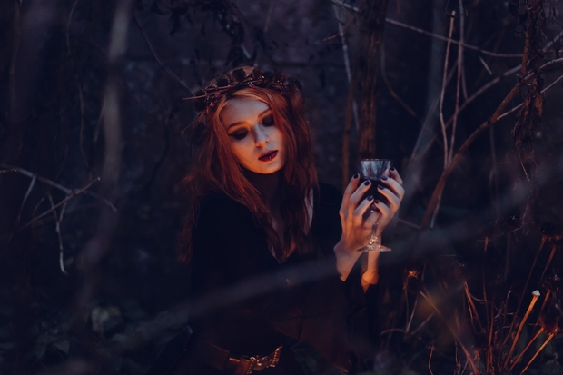 Woman dressed as witch holding a cup