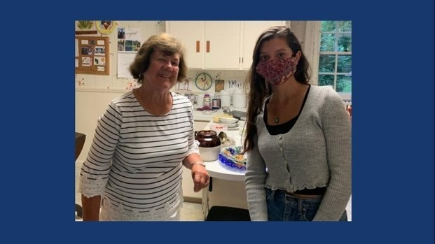 two women in a kitchen, one with a mask
