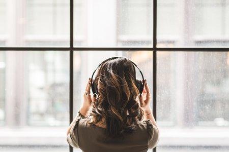 looking out window wearing headphones