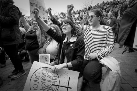 two women protesting on one knee with raised fists
