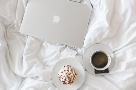 coffee, food and laptop spread on bed