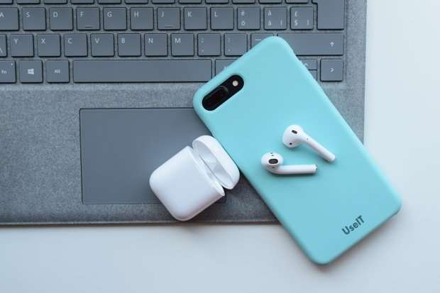 airpods and phone on laptop