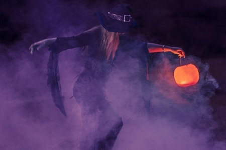 woman in witch costume surrounded by purple fog