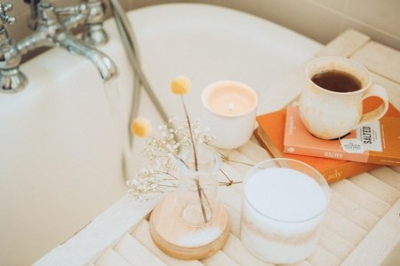 Tea cup and candle by a bath tub