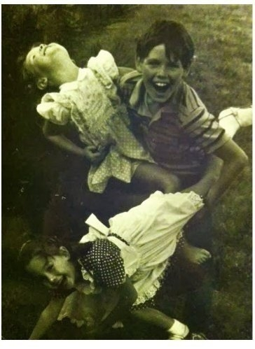 A black and white image of a young boy playing with two young girls