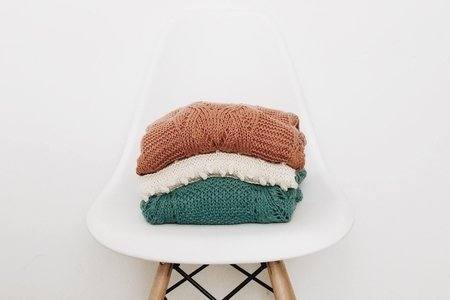 3 sweaters on white chair