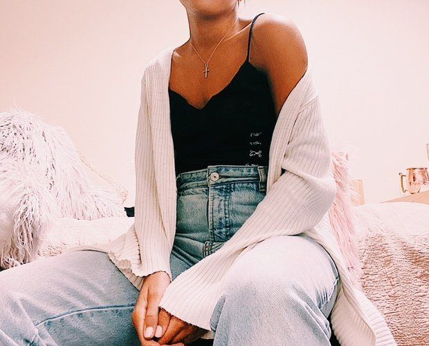 Woman wearing denim jeans, black tank top and a white cardigan