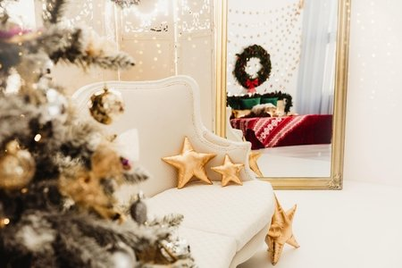 white couch with star-shaped pillows sits between a gold-framed mirror and a Christmas tree.